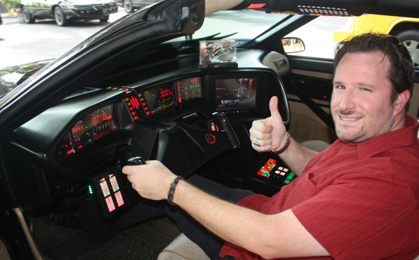 Host Steve Czarnecki sits inside one of the Knight 2000 cars during the Knight Rider 30th Anniversary event in Universal City