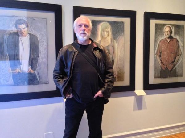 Drew Struzan posing amongst his posing portraits