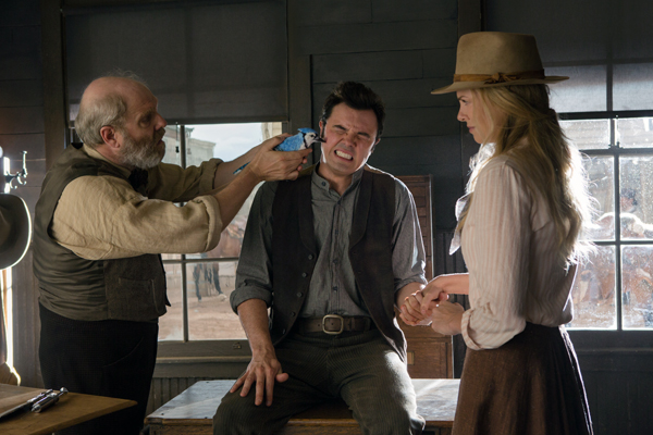Albert (MacFarlane) gets tended by a doctor while Anna (Theron) looks on
