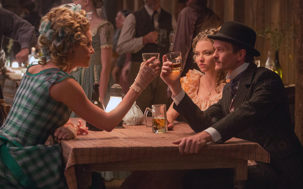 Anna (Theron) sits with Foy (Harris) and Louise (Seyfried) at a hoedown