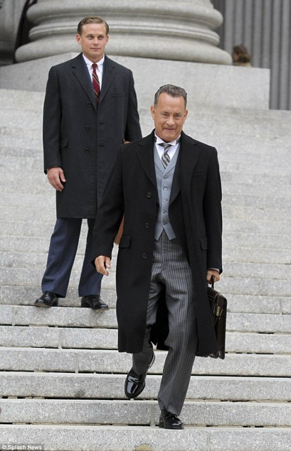 Tom Hanks in a traditional classic three-piece suit and a large black overcoat is joined on set by co-star Billy Magnussen