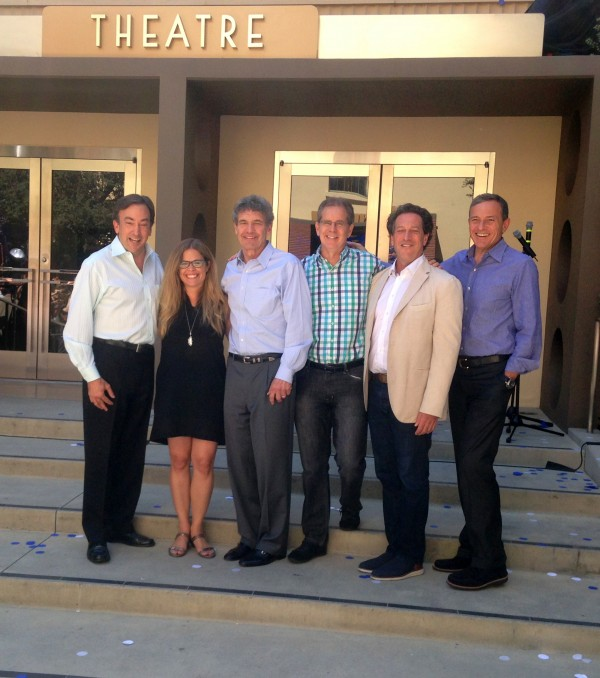 Execs and Filmakers stand below Elsa and Anna's image at the Walt Disney Studios theater