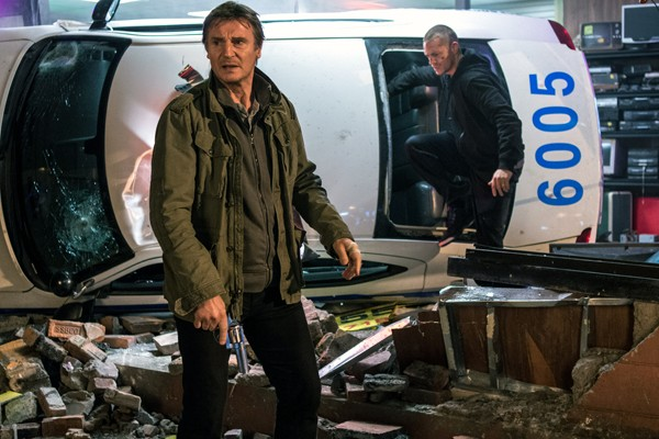 Jimmy (Neeson) and Mike (Joel Kinnaman) walk away from a wrecked police car