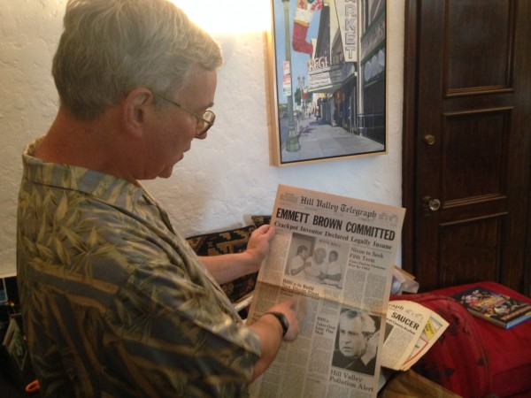 Bob Gale points out hidden details of one of the alternate time-line newspapers to a BTM crew member before the shoot.
