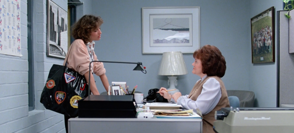 Edie McClurg in at the desk in the 1986 film talking to Jennifer Grey (aka Jeannie Bueller)