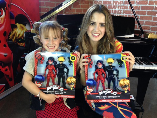 Lindalee Rose & Laura Marano hold up some Ladybug & Cat Noir toys given to them by Jeremy Zag, the Producer of Miraculous
